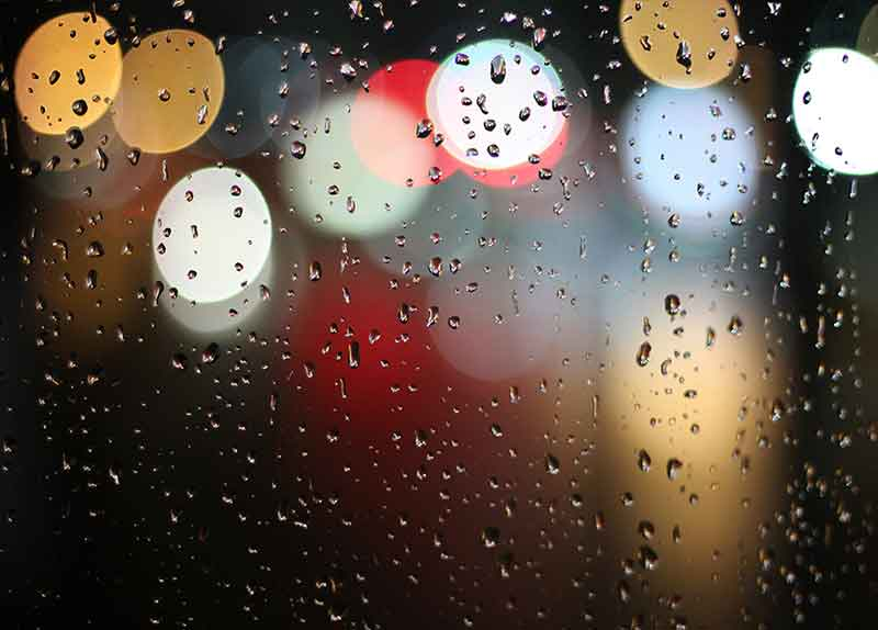 raindrops on window | looking out to road lights at night